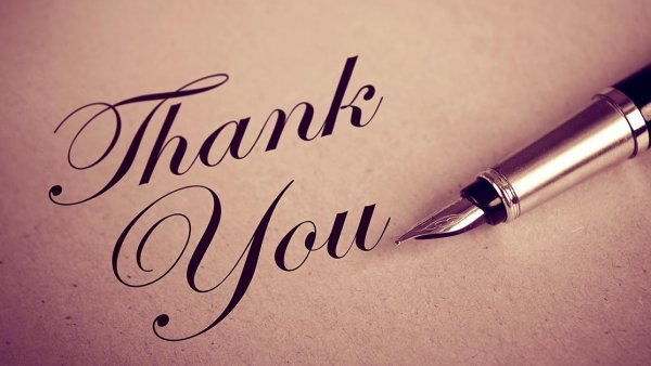 A thank you message written in cursive on parchment paper with a fountain pen laying beside it
